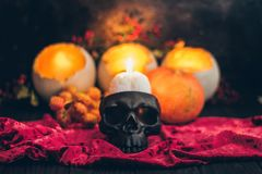 A ritual halloween witchcraft scene with candles, vintage cloth on the rustic background and a scary skull skeleton face. A ritual halloween witchcraft scene stock photography