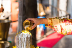 A ritual of Hindu religion. A solution of rice flour pours on the sculpture Lingam. Close-up. Royalty Free Stock Image