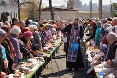 Ritual pascual ortodoxo tradicional - sacerdote que bendice el huevo de Pascua Foto de archivo libre de regalías