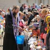 Ritual pascual ortodoxo tradicional - sacerdote que bendice el huevo de Pascua Imagen de archivo