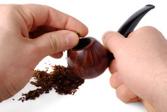 Ritual Preparation. Male hands filling up pipe with tobacco over white background Royalty Free Stock Images
