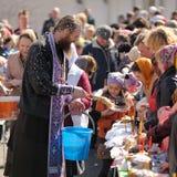 Rituale pasquale ortodosso tradizionale - sacerdote che benedice l'uovo di Pasqua Immagini Stock Libere da Diritti