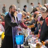 Rituale pasquale ortodosso tradizionale - sacerdote che benedice l'uovo di Pasqua Fotografie Stock