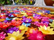 Ritualen som ber den färgrika stearinljuset som svävar på vatten för, ber buddha Royaltyfri Bild