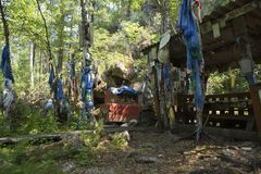 Rituals and religion. A sacred place of Buddhists in eastern Siberia. Colored Buddhist tags hang on the tree with prayer. Prayers and wishes on colored ribbons Stock Images