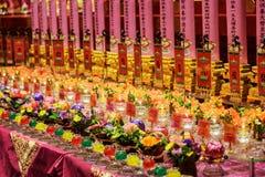 Ritualstearinljus och blommor, templet för Buddhatandrelik Arkivfoto