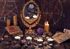 Rituel magique avec les runes, le miroir, les cartes de tarot et les bougies antiques Photographie stock
