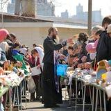 Rituel pascal orthodoxe traditionnel - prêtre bénissant l'oeuf de pâques Photos stock
