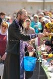 Rituel pascal orthodoxe traditionnel - prêtre bénissant l'oeuf de pâques Images stock
