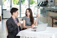 Riunione corporativa! Giovani persone di affari che si siedono alla tavola e Immagine Stock