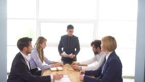 Riunione d'affari e negoziati di giovane uomo d'affari Il capo tiene una riunione nell'ufficio I colleghi discutono video d archivio