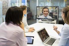 Riunione d'affari nell'ufficio, gruppo di persone di affari in video raggiro Immagine Stock