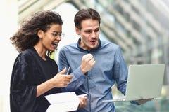 Riunione d'affari Uomo e donna che discutono lavoro e che esaminano lo schermo del computer portatile Lavoro insieme all'aperto fotografia stock libera da diritti