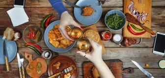 Riunione degli amici alla tavola di cena con gli spuntini ed il vino dell'americano Del pane tostato dei bicchieri di vino Fotografie Stock