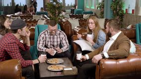 Riunione degli amici nel caff? Giovani che parlano e che mangiano pizza in un caff? stock footage