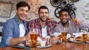 Riunione degli amici Uomini che si siedono nel pub della birra immagine stock
