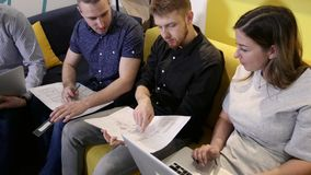 Riunione degli impiegati di concetto I colleghi discutono il piano che si siede sul sof? dalla tavola stock footage