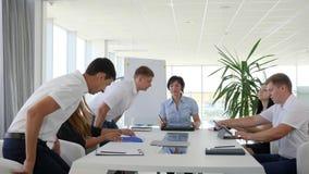 Riunione dei partner alla tavola per la discussione dello sviluppo di affari di idee nell'ufficio moderno stock footage