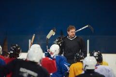 Riunione del gruppo dei giocatori di hockey su ghiaccio con l'istruttore Fotografia Stock