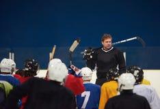 Riunione del gruppo dei giocatori di hockey su ghiaccio con l'istruttore Immagine Stock Libera da Diritti