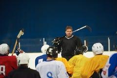 Riunione del gruppo dei giocatori di hockey su ghiaccio con l'istruttore Immagini Stock