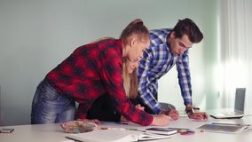Riunione del gruppo dell'architetto arredatore in ufficio creativo Giovani dei pantaloni a vita bassa che fanno gli schizzi che s video d archivio