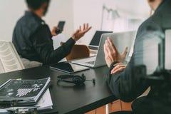 riunione di lavoro di co, uomo d'affari due facendo uso della cuffia avricolare di VOIP con latop Immagini Stock Libere da Diritti