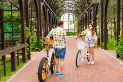 Riunione di una ragazza e di un tipo con le bici in arco Fotografie Stock Libere da Diritti