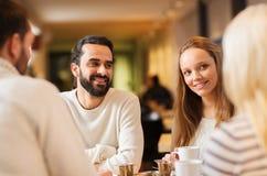 Riunione felice delle coppie e tè o caffè bevente Immagine Stock Libera da Diritti