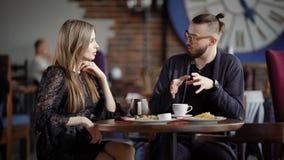 Riunione felice delle coppie nella caffetteria Colleghi che spendono l'intervallo di pranzo che considera insieme il loro affare  stock footage
