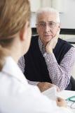 Riunione preoccupata dell'uomo senior con il dottore In Surgery Immagine Stock Libera da Diritti
