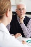 Riunione preoccupata dell'uomo senior con il dottore In Surgery fotografia stock