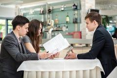 Riunione straordinaria! Un uomo d'affari di tre giovani che si siede ad una tavola dentro Fotografia Stock Libera da Diritti