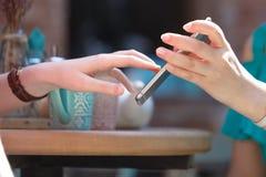 Riunione tra due persone Due giovani donne che si siedono alla tavola in caffè La ragazza mostra la sua immagine dell'amico sullo Fotografia Stock