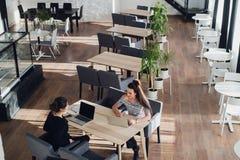 Riunione tra due persone Due giovani donne di affari che si siedono alla tavola in caffè La ragazza mostra le informazioni del co Fotografia Stock Libera da Diritti