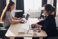 Riunione tra due persone Due giovani donne di affari che si siedono alla tavola in caffè Ragazza che per mezzo dello smartphone L Immagini Stock
