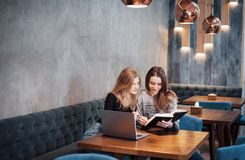 Riunione tra due persone Due giovani donne di affari che si siedono alla tavola in caffè La ragazza mostra le informazioni del co Fotografia Stock