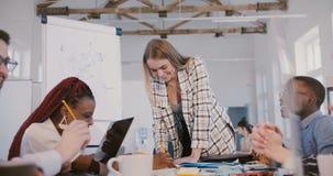 Riuscita bella giovane donna di affari positiva che sorride, impiegati multietnici creativi conducenti alla riunione dell'ufficio stock footage