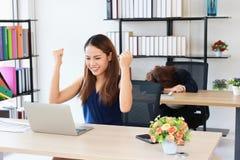 Riuscita donna asiatica di affari che solleva le mani con la curvatura del collega del concorrente giù la testa sullo scrittorio  immagini stock