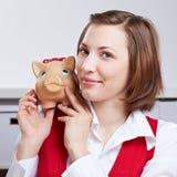 Riuscita donna con la banca piggy sopra Fotografia Stock