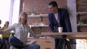 Riuscita donna di affari calma che si rilassa e che medita nel luogo di lavoro che si siede nella posa di yoga con gli occhi chiu stock footage