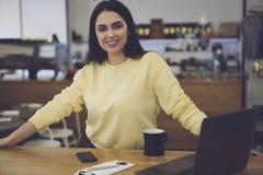 Riuscita donna di affari che considera macchina fotografica con il sorriso sul fronte Fotografie Stock