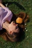 Riuscita donna di affari che si trova sull'erba con il cheesburger dell'hamburger degli alimenti a rapida preparazione su capelli fotografia stock libera da diritti