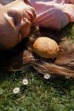 Riuscita donna di affari che si trova sull'erba con il cheesburger dell'hamburger degli alimenti a rapida preparazione su capelli immagine stock libera da diritti