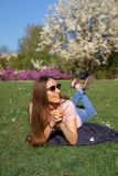 Riuscita donna di affari che si trova sull'erba che gode del tempo libero di svago in un parco con i ciliegi sboccianti di sakura immagine stock
