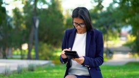 Riuscita donna di affari con il computer della compressa sul fondo verde del parco Bella ragazza in usura convenzionale e vetri archivi video