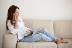 Riuscita elaborazione multitask della donna di affari che lavora dalla casa fotografia stock