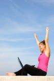 Riuscita giovane donna con il suo computer portatile Fotografia Stock