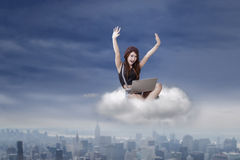 Riuscita ragazza castana con il computer portatile sulla nuvola Fotografia Stock Libera da Diritti