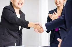 Riuscita stretta di mano asiatica della donna di affari dopo il contratto importante di discussione nel corso della riunione fotografie stock
